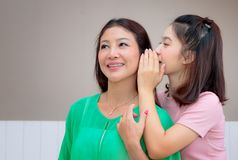 Asian mother and teen daughter whispering gossip. Happy Asian mother and teen daughter whispering gossip royalty free stock photo