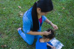 Happy asian mother ties  hair of her sun while the adorable male kid eating snacks royalty free stock images