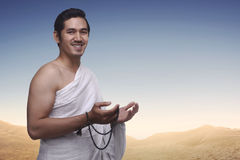 Happy asian muslim man wearing ihram clothes and prayer beads Royalty Free Stock Photo