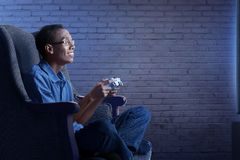 Happy asian nerd man in sofa with gamepad playing game Royalty Free Stock Image