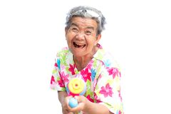 Happy Asian older woman playing water gun on white background Stock Photos