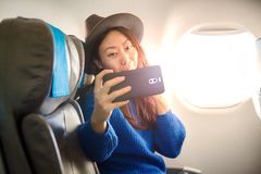 Happy Asian passenger sitting on a plane near the window and takes a selfie on your smartphone. royalty free stock images