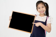 Happy Asian preteens girl hand holding wood board. On gray background with smile face Stock Photo