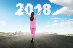 Happy New Year 2018. Happy asian runner woman looking 2018 number from clouds at sky. Happy New Year 2018 Stock Photo