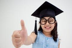 Happy Asian school kid graduate in graduation cap. With big thumb up Stock Images