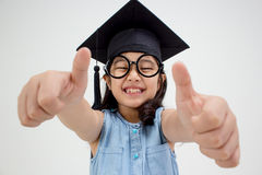 Happy Asian school kid graduate in graduation cap. With big thumb up Stock Photography