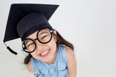 Happy Asian school kid graduate in graduation cap Royalty Free Stock Photos