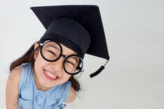 Happy Asian school kid graduate in graduation cap Stock Photos