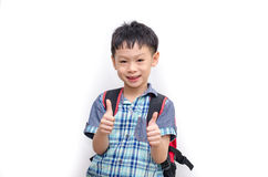 Happy Asian schoolboy wearing backpack and giving thumbs up Royalty Free Stock Images
