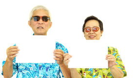 Happy Asian senior couple holding white blank sign ready for hol. Iday trip Royalty Free Stock Photos