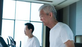 Happy Asian senior couple running on treadmill healthy lifestyle. Happy Asian senior couple running on treadmill together healthy lifestyle Royalty Free Stock Photos