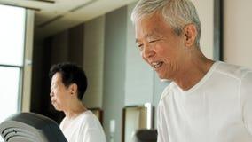 Happy Asian senior couple running on treadmill healthy lifestyle. Happy Asian senior couple running on treadmill together healthy lifestyle Stock Photo