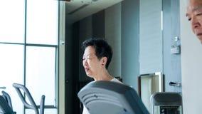 Happy Asian senior couple running on treadmill healthy lifestyle. Happy Asian senior couple running on treadmill together healthy lifestyle Stock Photos