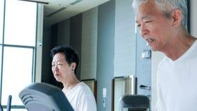 Happy Asian senior couple running on treadmill healthy lifestyle. Happy Asian senior couple running on treadmill together healthy lifestyle Royalty Free Stock Image