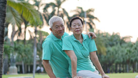 Happy Asian senior couple smiling after exercise in park Stock Images
