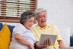 Happy Asian senior couple use tablet video chatting to family at home.aging at home concept.  stock photos