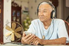 Happy asian senior man Headphones Listening Music. At home Royalty Free Stock Photo