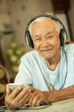Happy asian senior man Headphones. Listening Music at home Stock Image