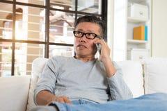 Happy asian senior man using Stock Images