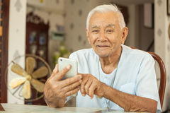 Happy asian senior man using the mobile phone Stock Photos