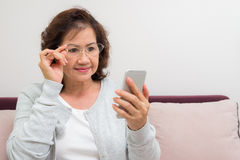 Happy Asian senior woman receiving new message on her phone Stock Photo