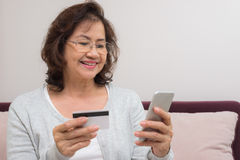 Happy Asian senior woman shopping online pay with credit card Stock Photography