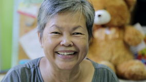 Happy asian senior woman smiling in front of camera. Happy asian senior woman is smiling in front of camera stock footage
