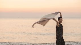 Happy Asian senior woman tun at beach with scarf fabric and copy space stock photos