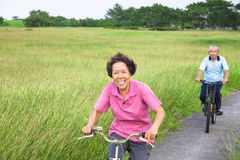 Happy asian seniors couple biking in the park. Royalty Free Stock Image