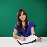 Happy Asian student writing on notebook, on green background Royalty Free Stock Photography