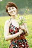 Happy Asian summer girl. Charming Asian girl holding rape flowers in rape field Stock Images