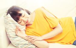 Happy asian teenage girl sleeping on sofa at home Stock Image