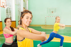 Happy Asian teenage girl warming-up in sports hall stock image