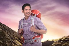 Happy asian tourist man with backpack climbing Royalty Free Stock Photos