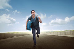 Happy asian tourist man carrying luggage running. Along the street Stock Photography