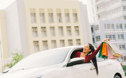 Happy Asian tourist woman raise shopping bags on modern white car, look up at copy space. Shopaholic consumerism activity stock photo