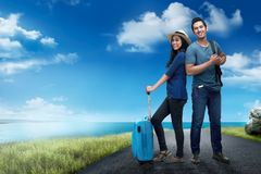 Happy asian traveler couple with bag standing on the road. With blue sky background Stock Image