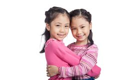 Happy Asian twin sisters hug each other. Isolated on white background stock photo