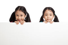 Happy Asian twins girls  behind white blank banner Stock Photography