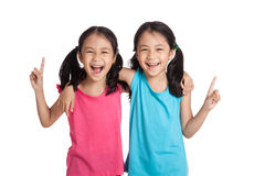 Happy Asian twins girls smile point up. Isolated on white background stock photo