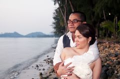 Happy Asian wedding couple in tropical location Stock Photography