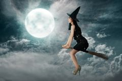 Happy asian witch woman flying above a broomstick stock photos