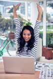 Happy Asian woman with arms raised looking at laptop Stock Photography