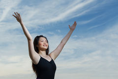 Happy Asian woman with arms raised upwards Royalty Free Stock Image