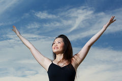 Happy Asian woman with arms raised upwards Stock Photography