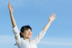 Happy Asian woman with arms raised upwards Stock Images