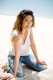 Happy asian woman by the beach. Happy woman kneeling on the beach in casual wear stock image