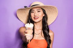 Happy asian woman in beach attire holding out an ice-cream cone and looking. At camera stock photos