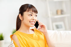 Happy asian woman calling on smartphone at home Royalty Free Stock Image
