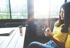 Happy Asian woman chatting on her mobile phone while relaxing in cafe during free time. Charming and beautiful hipster girl with smile reading good news on stock photo